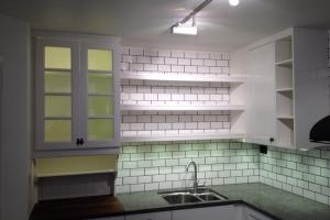 Sekelskifteskök med kaklad vägg och öppna hyllor